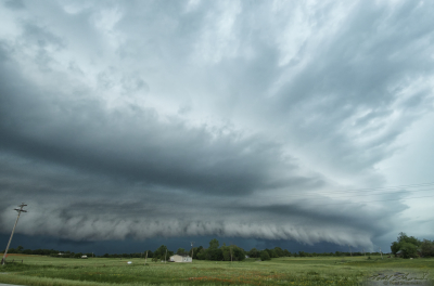 A pronounced shelf cloud develops as a supercell begins to turn outflow dominant, racing over central Oklahoma.