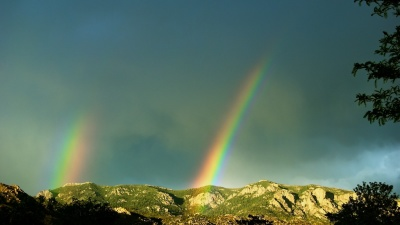 Dual rainbow segments over the Sandia mountains near Albuquerque.