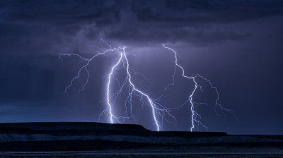 Lightning strikes just beyond a distant mesa in central New Mexico.