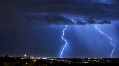 Dual cloud-to-ground lightning strikes are seen from the foothills in eastern Albuquerque.