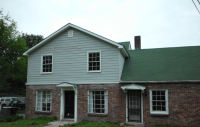 Exterior with new windows, siding and overhangs