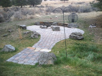 fire pit area with rock seating and pavers