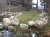 Boulder retaining wall and lifted lawn area