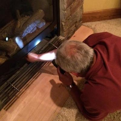 Chuck inspecting operation of a fireplace.