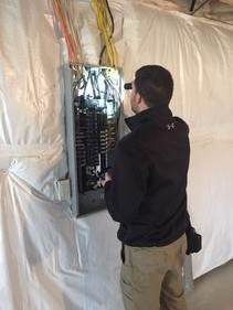 Chris checking an electrical panel.