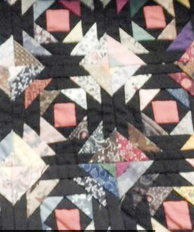 Photo snipit of a colorful, pieced quilt top (flying geese like pattern).