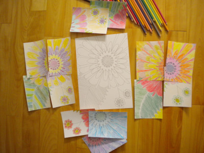 Picture of some Infinity Art LLC black and white cards with a large assortment of colored pencils.