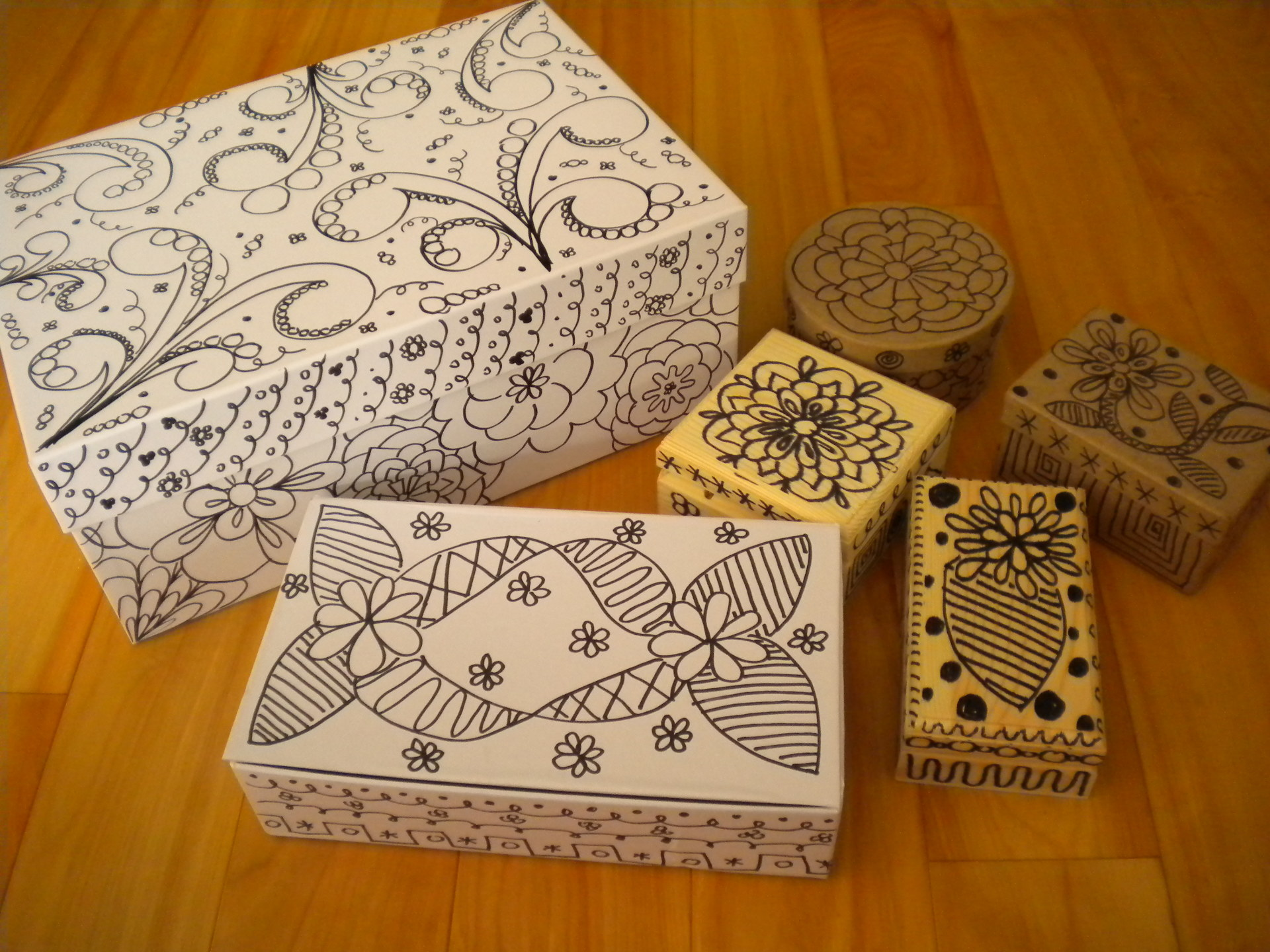 Photo of six boxes of different shapes and sizes covered in black and white artwork designs all over