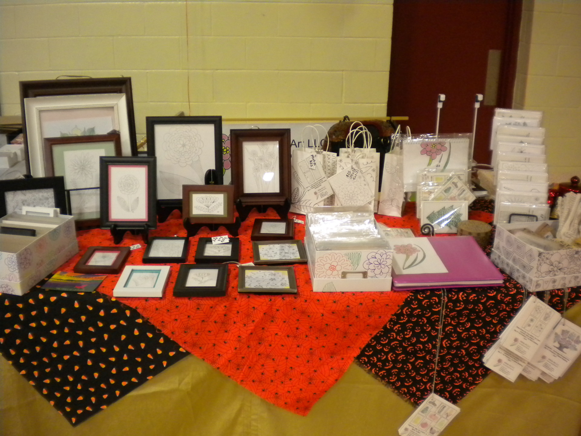 Colorful booth display with Halloween fabric and artwork framed, cards, color bags, and centerpieces