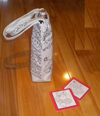 Picture of a fun art covered cloth wine/beer tote with two red heart coasters