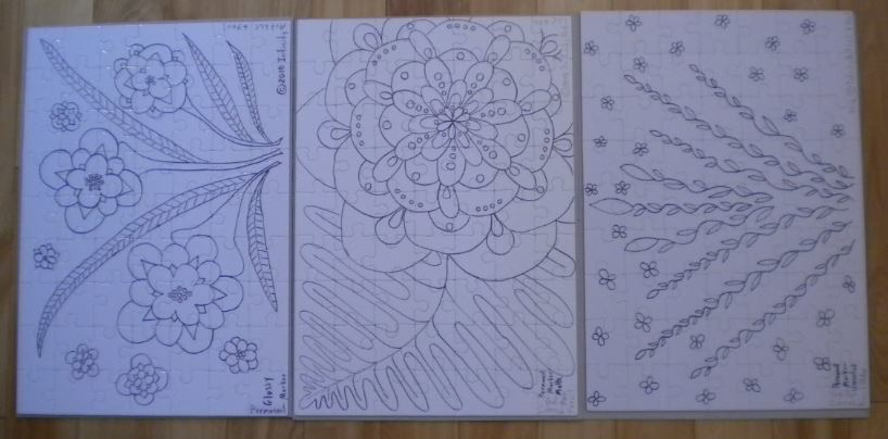 Photo of three puzzles with original artwork in black and white, that you get to color yourself.