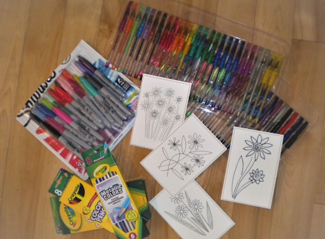Picture of some Infinity Art LLC black and white cards with an assortment of coloring instruments.