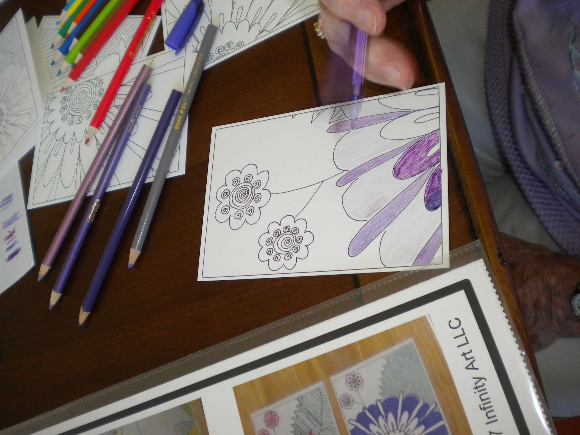 Photo of a coloring socialite working in purples on a floral postcard