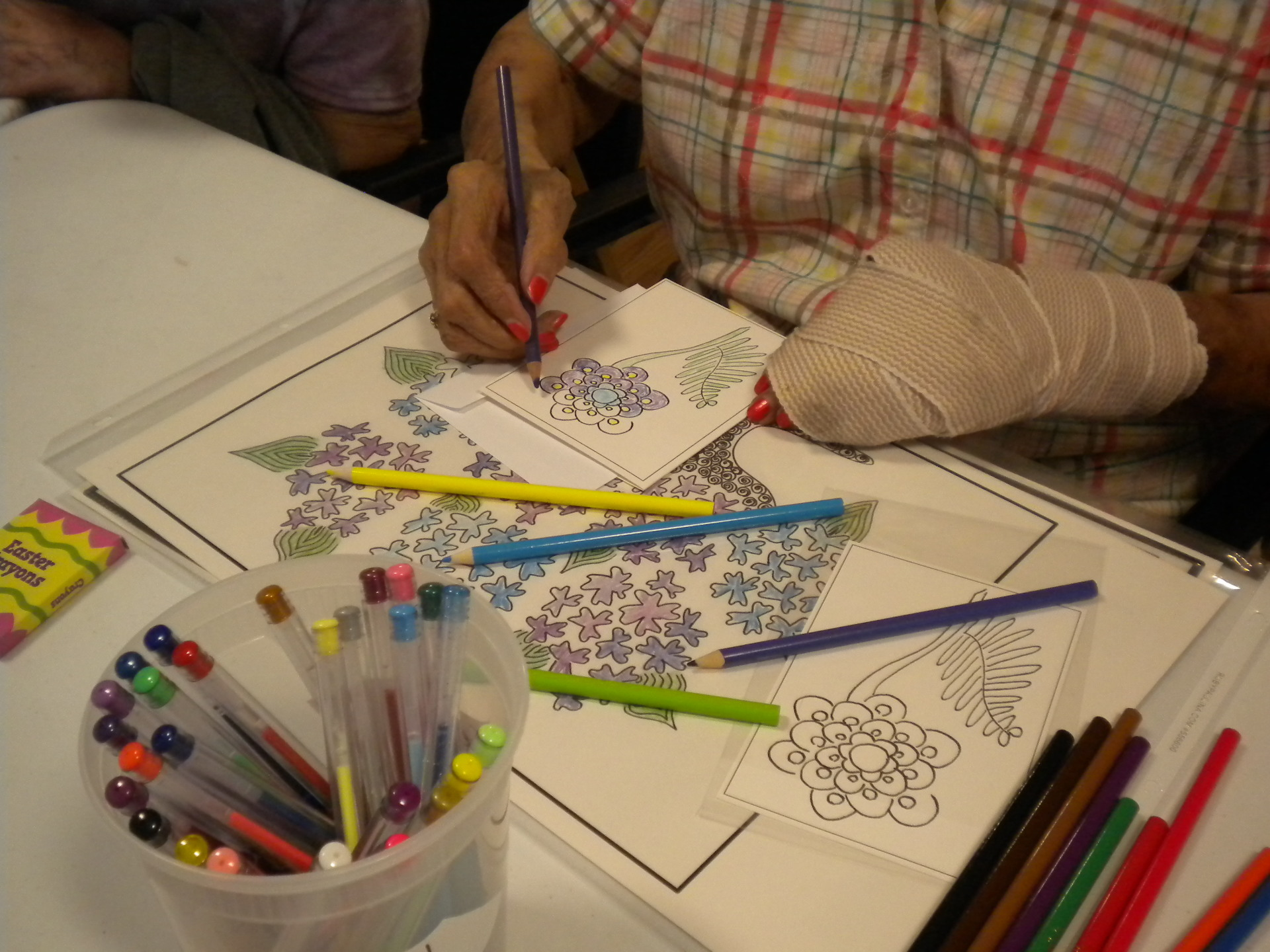 Photo of someone coloring blues and purples with the hydrangea bouquet one behind for inspiration.