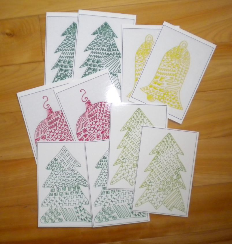 Photo of the Christmas Postcard set available on Etsy, 6 trees, two bells, and two ornaments in fun