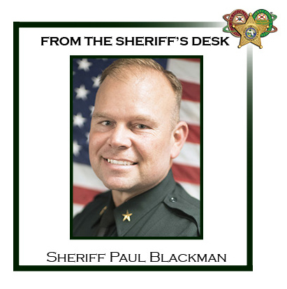 Sheriff Paul Blackman in front of American flag