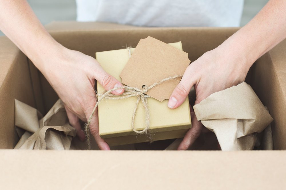 Woman placing a package containing art into a box from shipping