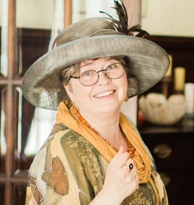 Artist Kathleen Black wearing a big hat in her bio page