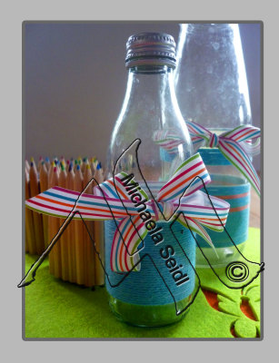 Bottles embellished with colorful yarn and ribbons