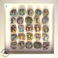 Calligraphy on pebbles, lombardic capitals in a frame by Michaela Seidl