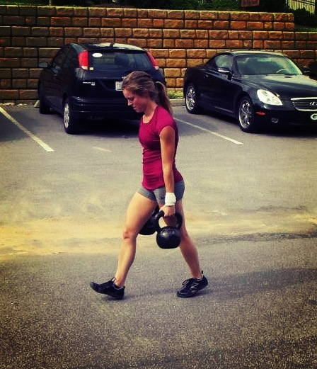 Crossfit female walking with kettle bells
