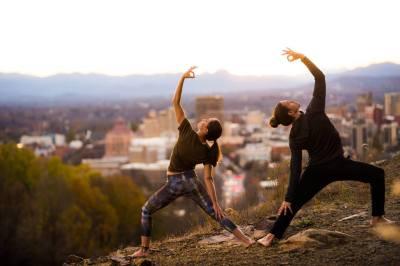Asheville Yoga Center women doing yoga with Asheville skyline in background