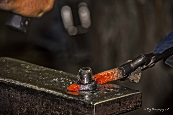 Hammering a drift through a hot, steel railroad spike to create a hole to form a bottle opener.