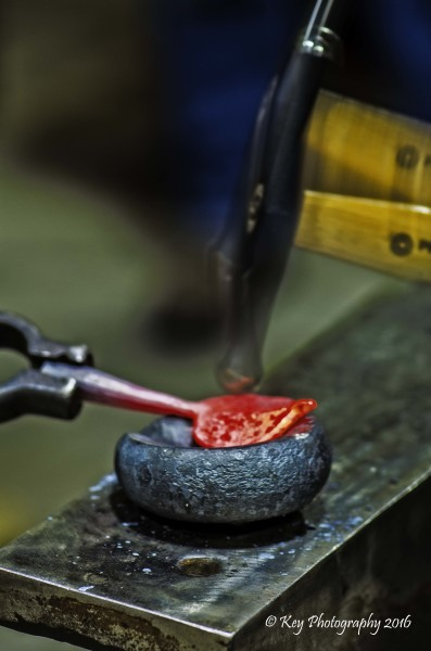 Picture of Hammer hitting hot steel leaf shape to curve the leaf
