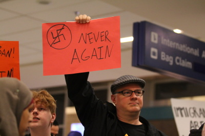 """A protester holds a sign depicting a swastika that says """"Never Again"""" during a protest at D/FW airport on January 29, 2017 in response to an executive order from President Trump restricting immigration from seven predominantly Muslim countries. (Anthony Mazur/AM News Net)"""