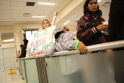 A protester holds a sign offering free hugs during a protest at D/FW airport on January 29, 2017 in response to an executive order from President Trump restricting immigration from seven predominantly Muslim countries. (Anthony Mazur/AM News Net)