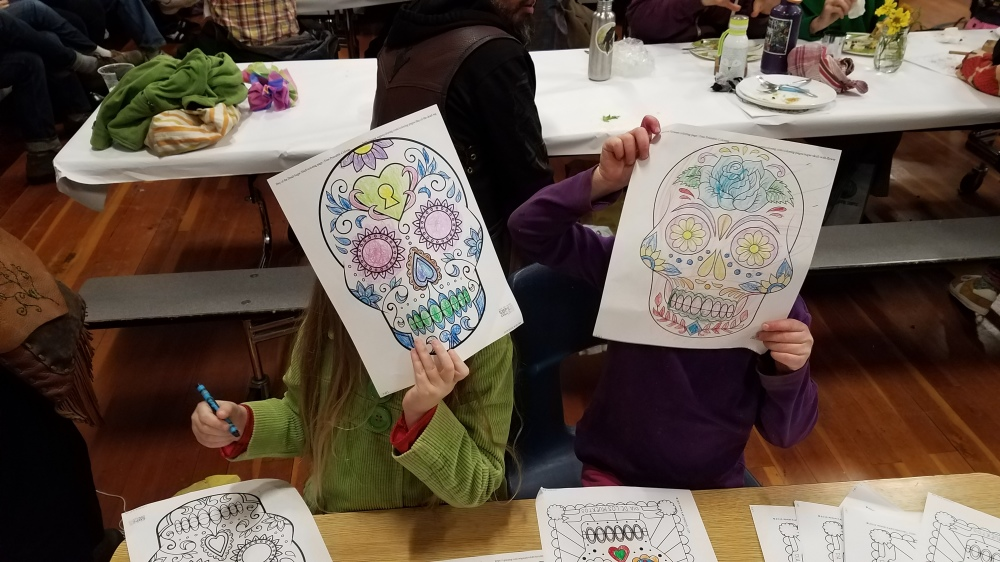 Students pose with their calaveras coloring sheets [click image to see entire picture]