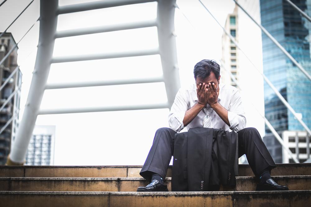 Depressed man contemplates his bankruptcy