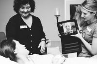 doula helping dad see baby born