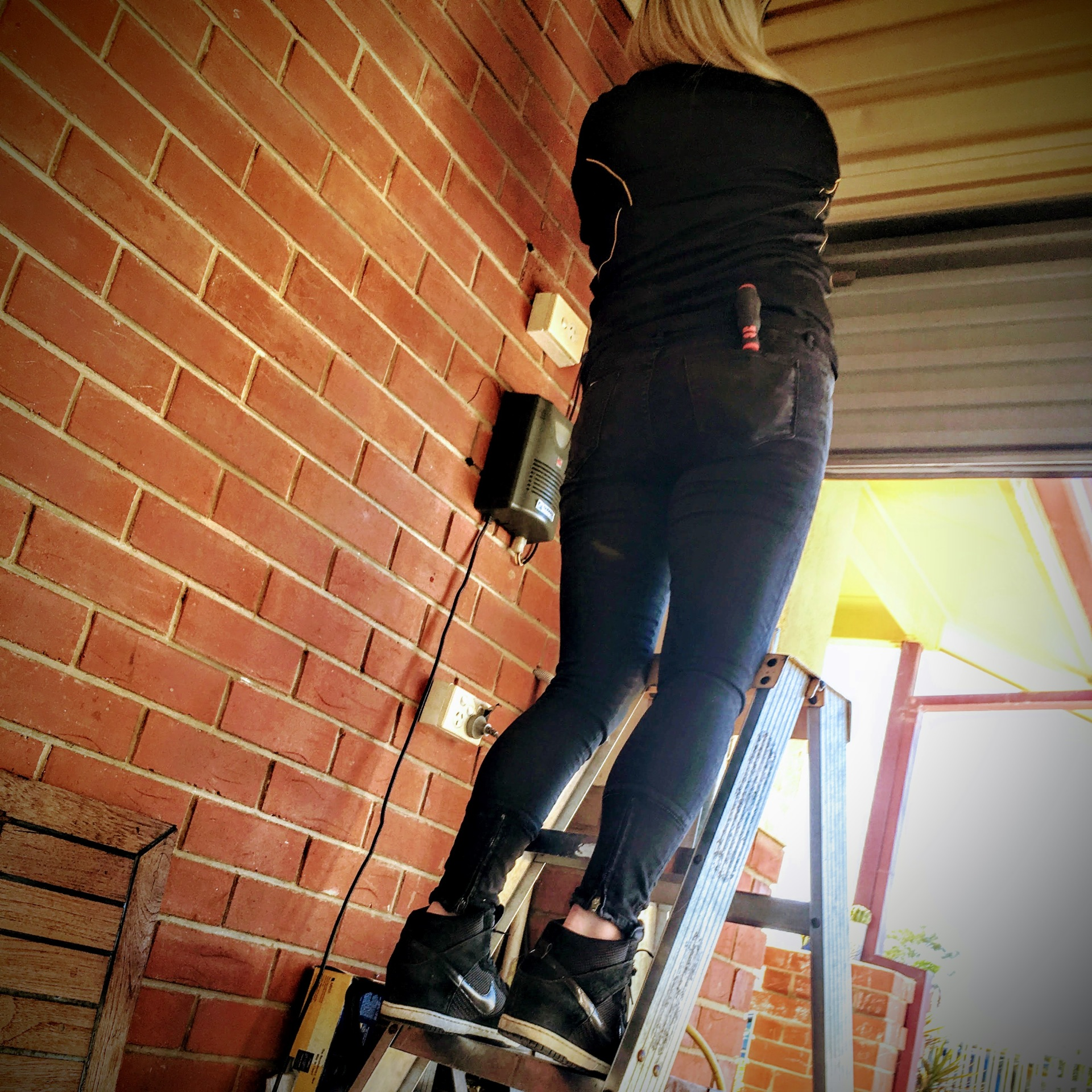 Our senior garage door technician Sara adjusting a Glidermatic roller door opener