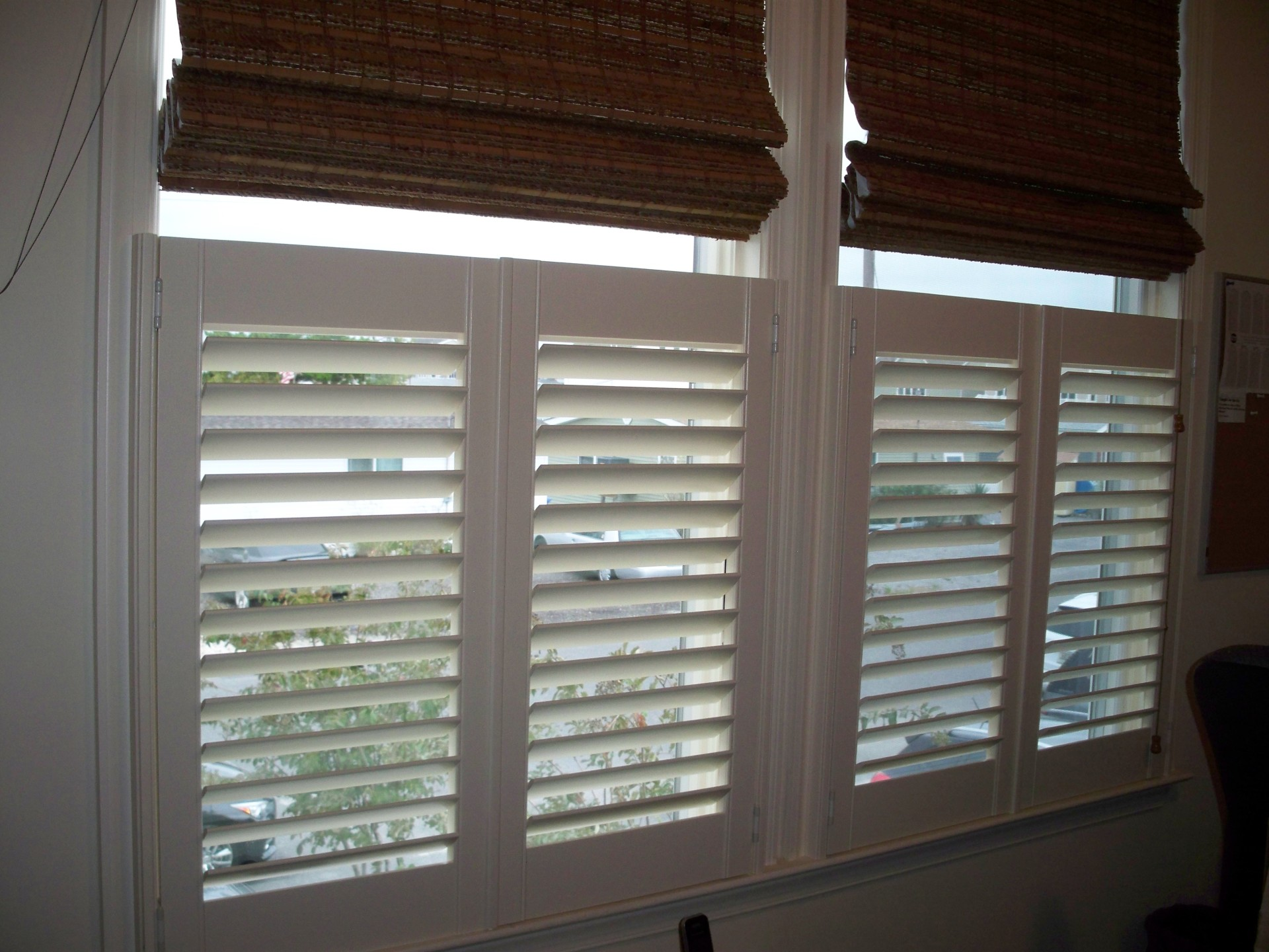 Shutters with woven roman shades