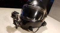 Photo of a black scorpion modular helmet with a go pro camera attached to the front and a Sena Bluetooth headset attached to the side.