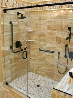 A shower makeover in Sarasota Florida with Frame-less glass shower doors and body sprays. A convenient ease of access to the shower is a safer design with grab bars, shampoo niche and hand held shower sprayers.