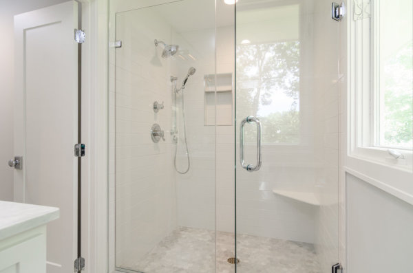 Shower remodel in Sarasota Florida with frame-less shower glass, hand held shower and diverter. Plumbing installation included shower body spray jets and overhead rain shower head.