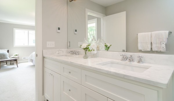 Bathroom remodel in Sarasota with custom made vanity cabinet in European style frame-less construction, marble countertop, and rectangular sinks.