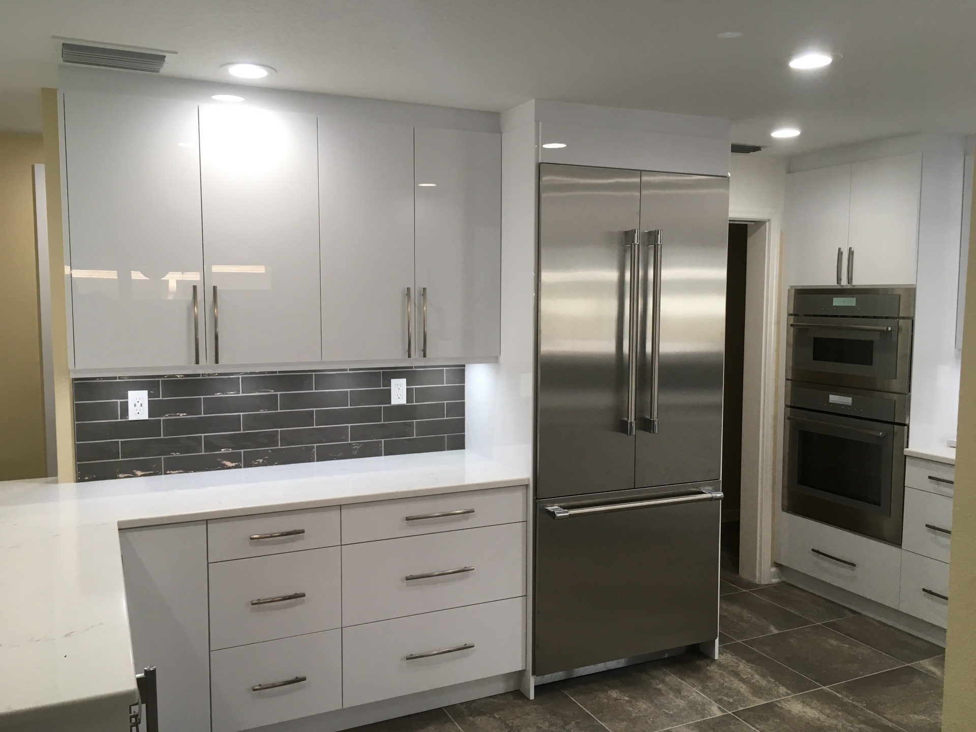 Custom made White Acrylic kitchen cabinets with cabinet depth refrigerator.