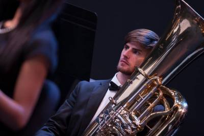 classical music male musician with tuba on stage