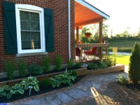 Red brick Farmhouse landscaping with grey flagstone and red brick walkway and hostas