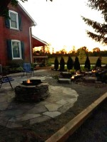 Stirling Ontario Farmhouse Landscaping picture with flagstone fire pit and pondless waterfall at dusk