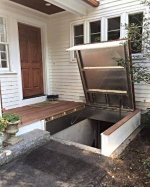 LuciGold All Aluminum basement bulkhead door hidden under a wooden deck