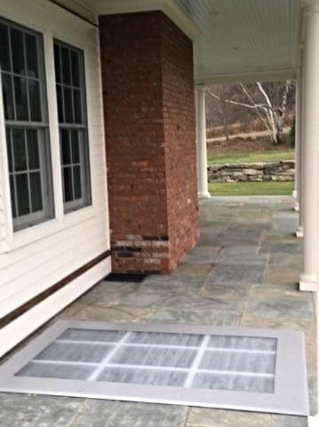 LuciGold lightweight all aluminum basement bulkhead door, flat profile on stone patio.