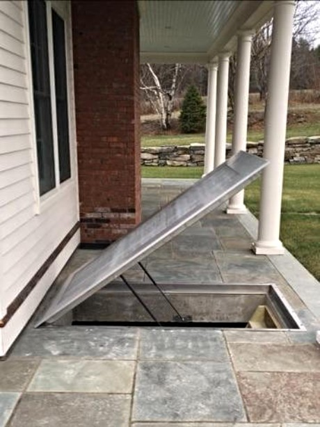 LuciGold lightweight all aluminum basement bulkhead door, flat profile on stone patio. door open