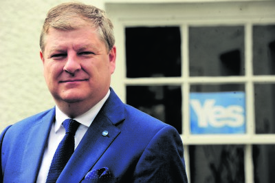 Angus Robertson in front a window with a Yes sign in it
