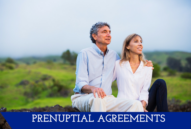 "A couple sits on the ground happy with their arms around each other.  They look off into the distance.  A banner at the bottom reads ""Prenuptial Agreements."""