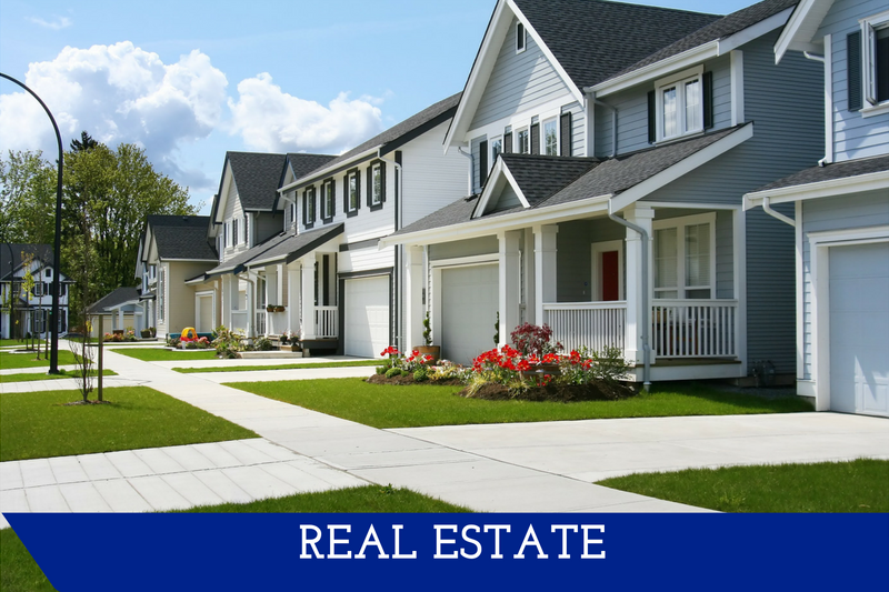 """A picture of a neighborhood street.  All of the houses' yards look clean, bright and well kept.  A banner at the bottom reads """"Real Estate."""""""