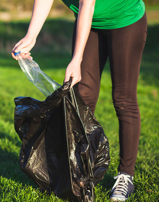 Young woman picking up trash and placing it in a trash bag